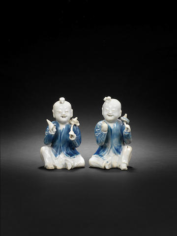 A rare pair of blue and white seated boys Circa 1750