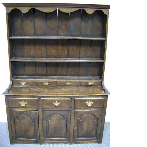 An 18th century style oak Welsh dresser with plate rack and three drawers above cupboards, 132cm wide 182cm high