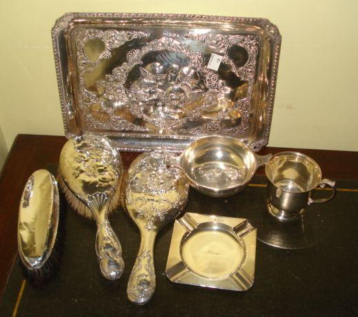 A silver dressing table tray, the central panel of winged cherubs heads within scrolling borders, Birmingham 1903, a matching silver backed hand mirror and hair brush, a silver christening mug with scroll handle, 1926, a Scottish two handled quaiche dish, 1883, a square ashtray, 1904 and a silver backed clothes brush, 27ozs weighable.