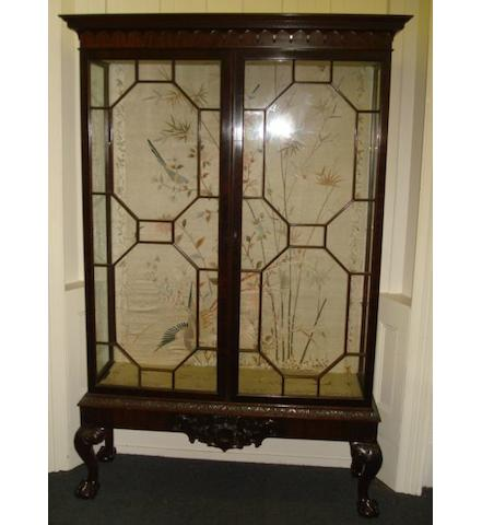 A good 'Chippendale Revival' carved mahogany display cabinet, lined in Oriental silk and finely embroidered with birds amongst flowering bamboo, fitted with plate glass shelves enclosed by a pair of glazed astragal doors, having a leafy scroll carved apron, on foliate carved cabriole legs, ball and claw feet, 131cm.