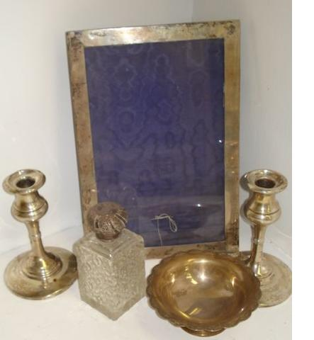 A George V large plain rectangular silver mounted easel photograph frame, Birmingham 1911, sight size 27 x 16.5cm, a pair of silver dwarf candlesticks, Birmingham 1915, a silver mounted cut glass toilet water bottle and a silver pedestal bon bon dish.