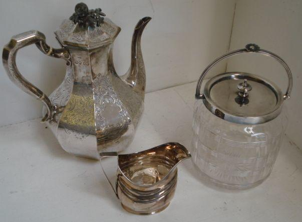 A Victorian silver octagonal coffee pot, William K Reid, 1844, the sides engraved with flowers, leafy scrolls and diaper around two vacant cartouches, hinged cover, associated plated cast finial, a George III silver helmet milk jug, 1803, makers mark worn, having panelled sides, 26ozs weighable, and an electroplate mounted glass biscuit barrel. (3)