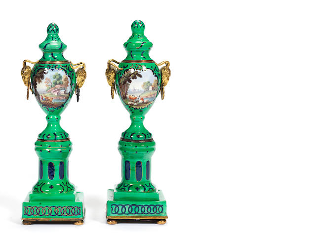 Pair of Casoulette vase/candlesticks, green and blud ground and panels of rustic scenes (some restoration)