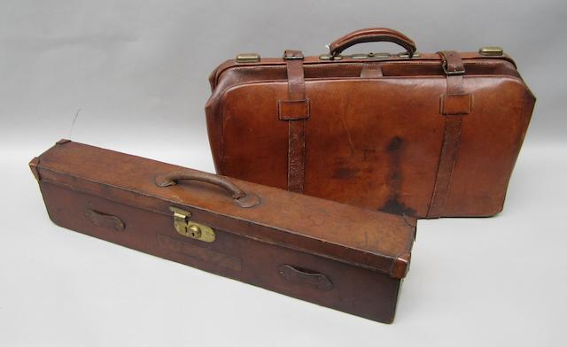 A brown leather Gladstone bag and a shotgun case,