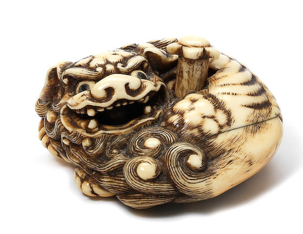 An unusual ivory netsuke of a recumbent shishi Late 18th century
