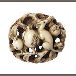 An ivory netsuke of a rat on pomegranates