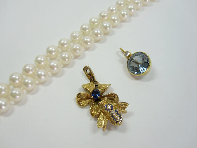 A long single-strand of pearls together with blue topaz and diamond enhancer and a sapphire bee and diamond enhancer