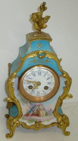 A late 19th Century French porcelain gilt metal mounted mantel clock, the shaped case with shaded turquoise ground painted with a courting couple, signed, the 8 day movement striking on a gong and stamped 'M E Daille D'argent', 32cm.