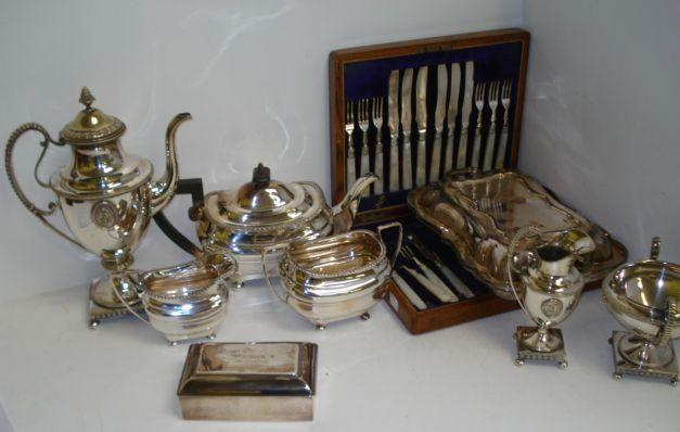 An Edwardian silver rectangular table cigarette box, makers mark rubbed, Birmingham 1907, the solid hinged gilt lined cover inscribed, 14.5 x 9cm, and the following electroplate :- an Empire style three piece coffee service, of classical vase form with applied cameo ovals, a Regency style three piece tea service by Walker & Hall, a shaped rectangular two handled entree dish, oak cased part set of mother of pearl handled fruit eaters, a tankard and a fruit dish.