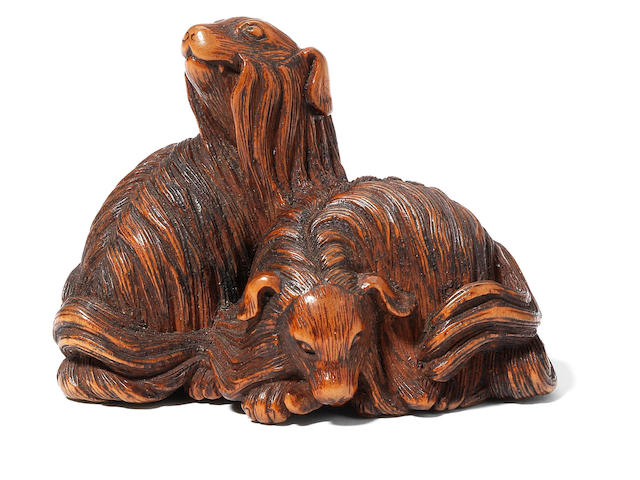 A large wood netsuke of two shaggy dogs (nouken or mukuinu) By Nobumitsu, 19th century