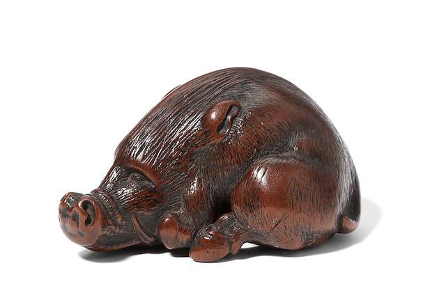 A wood netsuke of a recumbent wild boar By Masakazu, Nagoya (1839-1891), 19th century