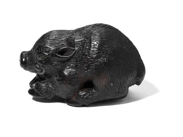 A wood netsuke of a recumbent wild boar After Tanaka Minko, 19th century