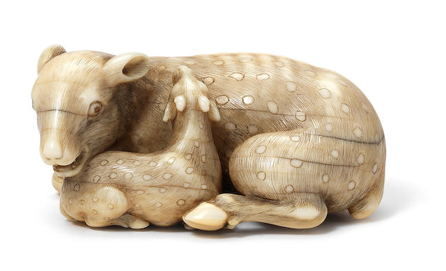 An ivory netsuke of a doe and young By Okatomo, Kyoto, 19th century