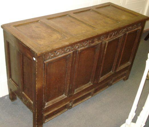 An early 18th Century oak mule chest, of panelled construction, now adapted as a cupboard, with a fixed top and enclosed by a pair of doors, two drawers under, the leaf scroll carved frieze with initials and date E.E. 1706', 146cm.