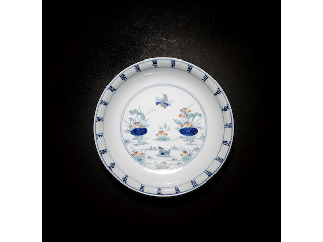 An elegant doucai dish of circular form decorated with a pair of mandarin ducks beside lotus Chenghua six-character mark but Kangxi or Yongzheng
