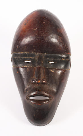 A carved and patinated wooden mask, Dan, Ivory Coast