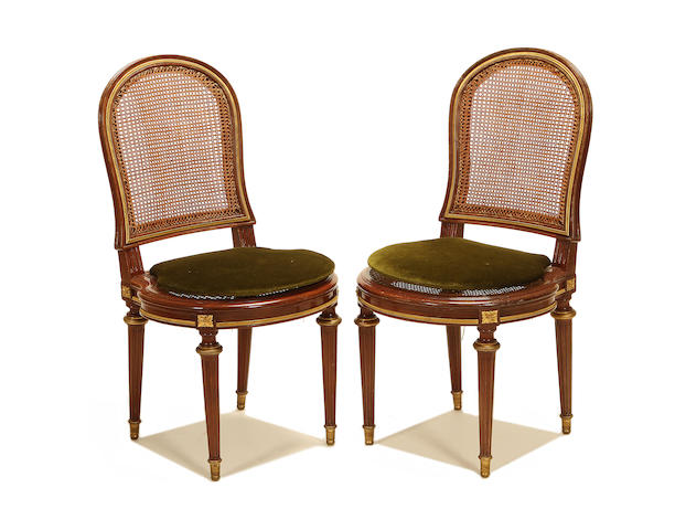 A set of twelve French late 19th/early 20th century gilt metal mounted mahogany caned side chairs in the Louis XVI style