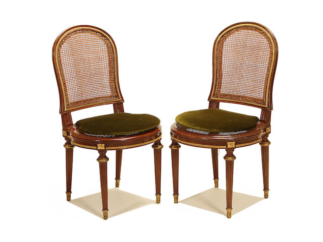 A set of twelve French late 19th/early 20th century gilt metal mounted mahogany and caned side chairs in the Louis XVI style