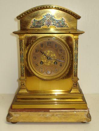 A 19th Century French brass cased mantle clock, the circular dial with Arabic numerals, the arch top case with champleve enamel panels, on giltwood plinth. (2)