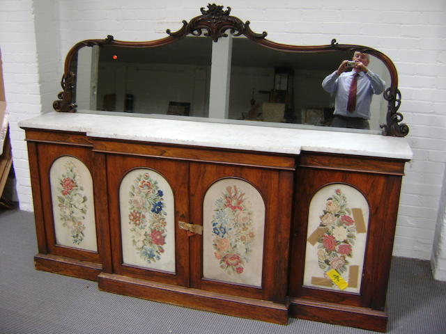 An early Victorian rosewood large chiffonier/sideboard, of breakfront form, each of the four etched front panels containing a different petit point floral reserve, white marble slab, leaf carved mirrored back, 215cm wide, 166cm high