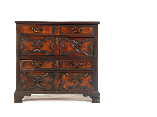 An oak and walnut two part 17th century geometrically moulded chest of drawers