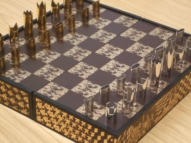 "A ""Spassky-Fischer Escher Horsemen/Metamorphosis"" silver and silver-gilt chess set, by Cy Endfield, 1973, from an American limited edition of 325 sets,"
