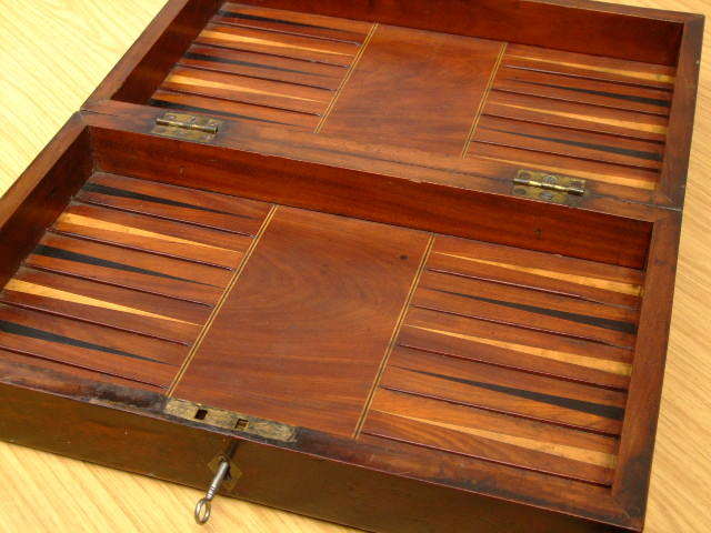 A George III mahogany, boxwood, ebony and ivory inlaid games board/box, circa 1800,