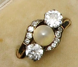 A diamond and pearl three stone ring of crossover design
