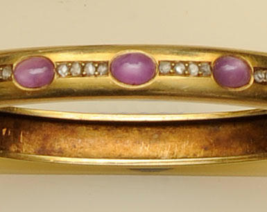 A late 19th Century gold mounted star ruby and diamond hinged bangle