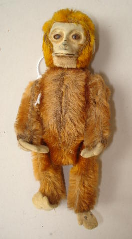 Miniature Schuco monkey perfume bottle, The orange plush monkey with metal face and brown eyes, felt ears, hands and feet, head lifts off with cork stopper, (colour faded to body), 13cm tall.