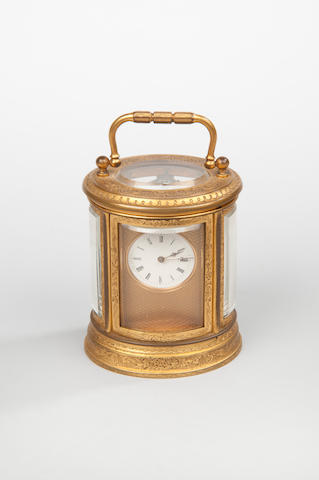 An early 20th century French miniature oval gilt brass carriage timepiece