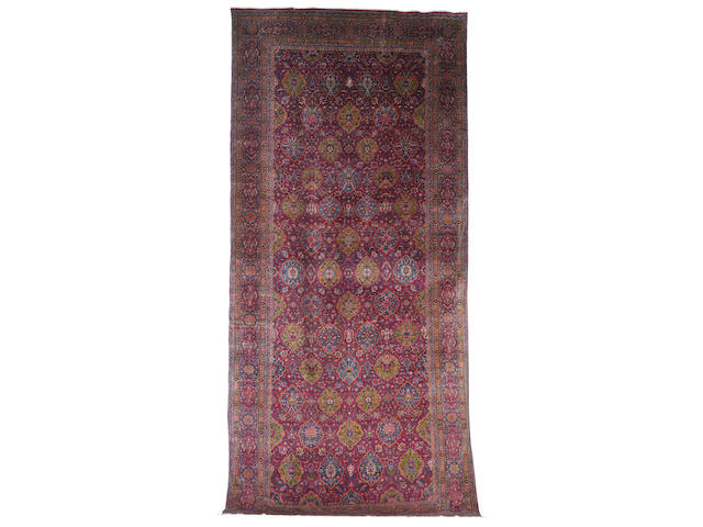 A large Kirman carpet, South East Persia, circa 1900, 23 ft x 10 ft 6 in (701 x 323 cm) some minor wear