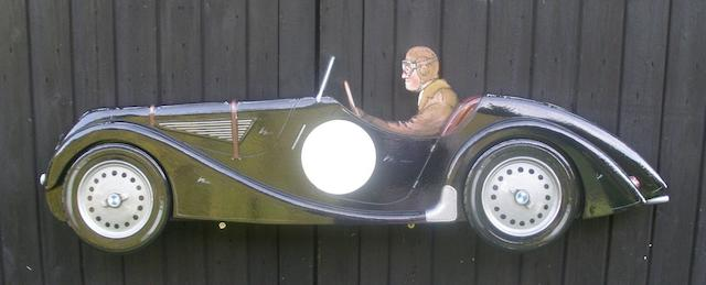 A hand-painted wooden profile of a BMW 328,