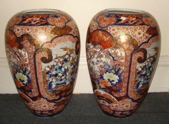 A large pair of Japanese Imari inverted baluster vases,Meiji, painted in typical palette with alternating panels of birds amongst flowering peones and cherry blossom with fan shape vignettes and a group of children around a fish tank on a gilded ground, floral and brocade ground, below an upper frieze of Jui-heads and ho-ho birds, 63cm, six character marks.