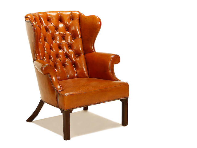 A Victorian mahogany and leather upholstered wingback armchair in the George III style