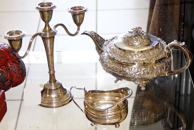 A George IV silver melon shaped teapot,with repousse decoration, London 1823, 25ozs and a silver small candleabra, Birmingham 1964, 23cm high and a Georgian silver cream jug (3).