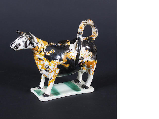 A Staffordshire Prattware cow creamer and cover, late 18th century