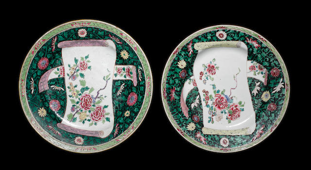 A pair of famille rose plates, decorated with floral designs on the black ground