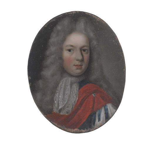English School, circa 1715 A Gentleman, wearing blue coat, slashed at the sleeve to reveal white, white lace cravat, a red mantle secured with a tiny brooch at his left shoulder, long powdered wig