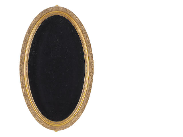 An oval portrait miniature wall cabinet of gilded wood, with glazed hinged door and blue velvet lining. The obverse with foliate and scrolling acunthus leaf border. Oval, 512mm (20 3/16in) high, 307mm (12 1/16in) wide, and 66mm (2 5/8in) dia.