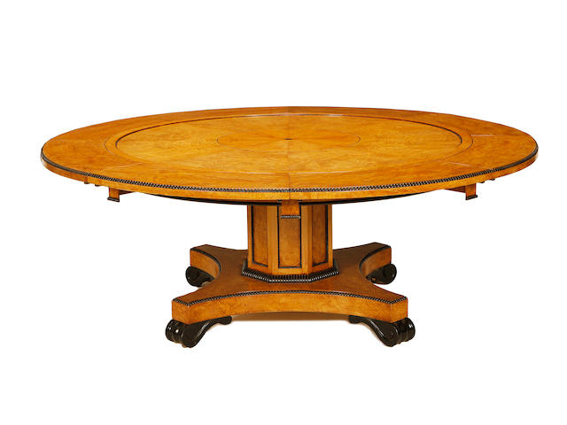 A large pollard oak and ebonised extending circular dining table
