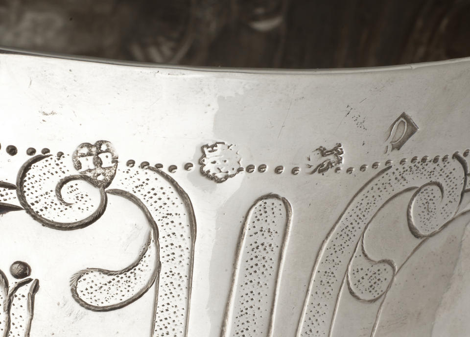 A Commonwealth silver two-handled porringer, maker's mark distorted by decoration possibly H P(?) or KF in a heart-shaped punch with two pellets above an one below, London 1657,