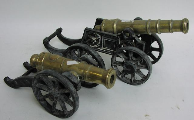 A pair of cast brass cannon on metal carriages 18x5.5x8.5ins (46x14x13cm) & 13x6x6ins. (33x15x15cm) 2