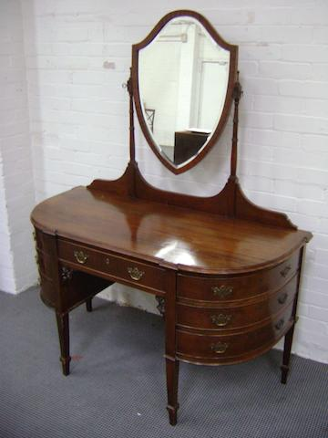 A Gerogian style mahogany dressing table with shield shaped swing plate and an arrangement of seven drawers, 133cm wide