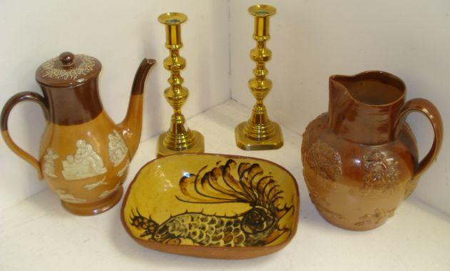 A collection of Royal Doulton, Doulton Lambeth and other stoneware, typical harvest decoration, including a coffee pot and baluster shape jugs, in various graduated sizes, a slipware dish and a pair of Victorian brass turned column candlesticks.