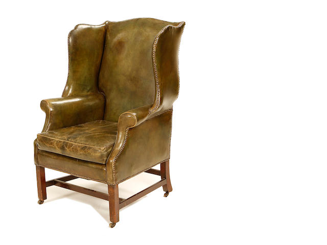An early 20th century leather upholstered reading chair in the George III style