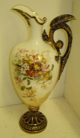 A good Royal Worcester ewer, shape 2156, well painted with a spray of summer flowers above a sepia Italianate landscape, on a circular pedestal foot, and gryphon moulded handle in blue and gilt, date mark for 1901, 34cm.