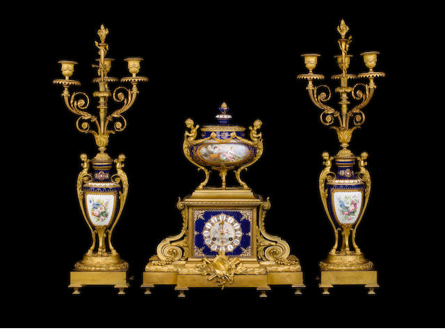 A French late 19th century ormolu-mounted, paste-set and parcel-gilt blue-ground Sèvres style porcelain clock and garniture