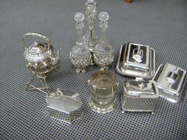 Electroplate wares comprising: a Victorian three bottle decanter frame, a tea kettle on lampstand, a pair of entree dishes, two biscuit boxes, and a siphon stand (6)