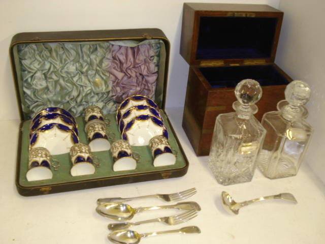 A cased set of six Edwardian Coalport coffee ans and saucers, the silver mounts embossed with putti in a classical landscape, Chester 1904, retailed b Jays, brass bound oak campaign style decanter box, by Army & Navy C.S.L. containing a pair of square glass decanters and two silver decanters labels, and a similar style canteen by the same makers, baize lined with two lift out trays, containing a part canteen of Elkington & Co fiddle & tread electroplate flatware, fifty five pieces, engraved with the 'Firebrace' crest and twelve further items of electroplate flatware.
